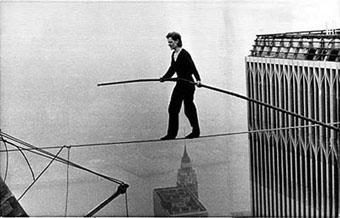 Philippe Petit op 415 meter hoogte. Let op het miniscule topje van het Empire State Building onder hem.